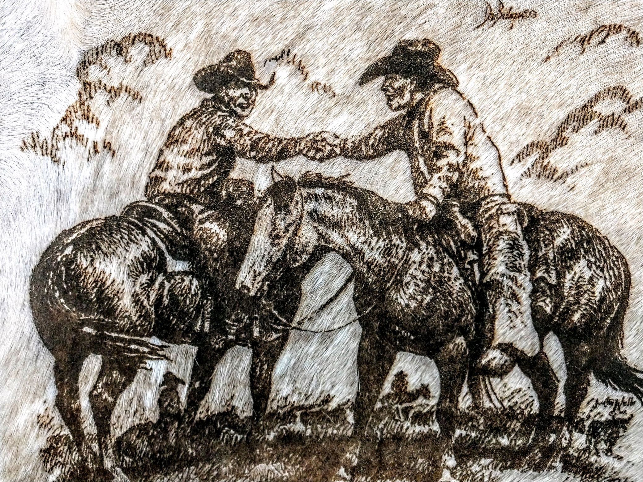 two ranchers on horseback shaking hands